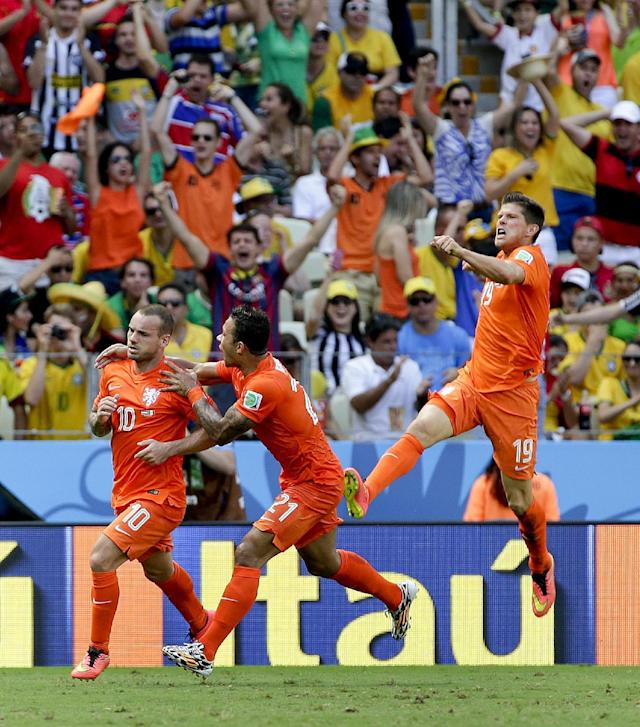Netherlands' Wesley Sneijder (10) celebrates with teammates Memphis Depay and Klaas-Jan Huntelaar (19) after scoring his side's first goal during the World Cup round of 16 soccer match between the Netherlands and Mexico at the Arena Castelao in Fortaleza, Brazil, Sunday, June 29, 2014. (AP Photo/Felipe Dana)