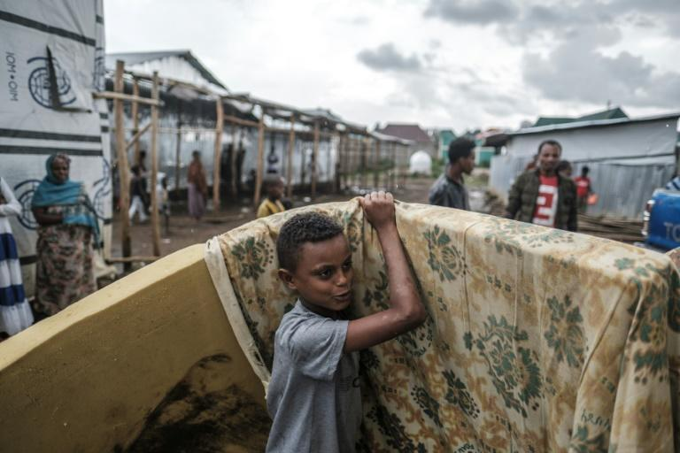A young boy takes a mattress handed out by an aid group at the Azezo camp