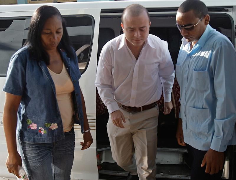 FILE - In this Oct. 5, 2012 file photo, Cuban security forces escort Spanish citizen Angel Carromero, center, to the courthouse in Bayamo, Cuba. Carromero.  The Spaniard who was sentenced in Cuba to prison in the death of a prominent dissident will fly back to Spain to serve the rest of his four-year term. Carromero, a Spanish regional political youth leader, was driving a car July 22 that lost control and crashed, killing Oswaldo Paya, a passenger. Paya was a well-known opponent of the Cuban government. (AP Photo/Ismael Francisco, Cubadebate, File)