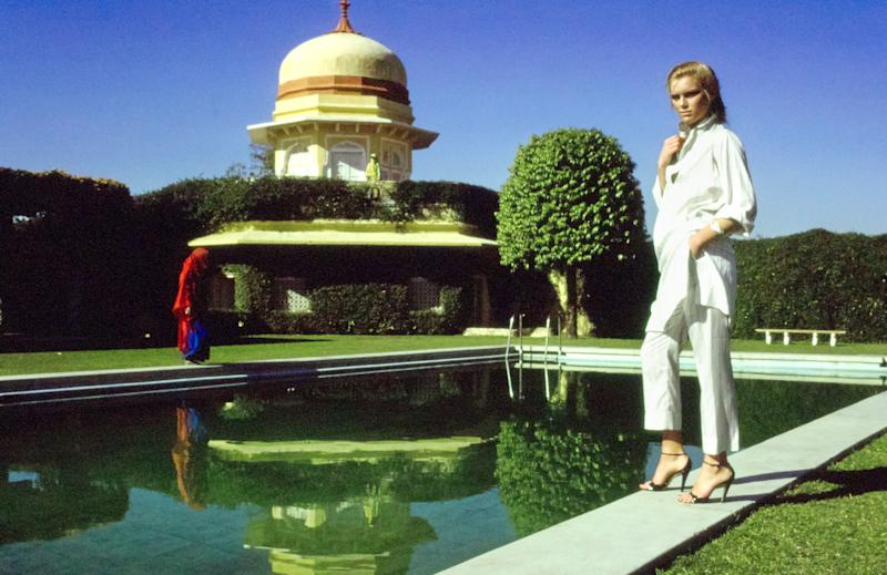 Model, Patti Hansen wearing Emanuel Ungaro narrow silk ankle-pants and thin shirt-tunic in cream and coffee stripes, standing poolside at India's Rajmahal Palace Hotel.
