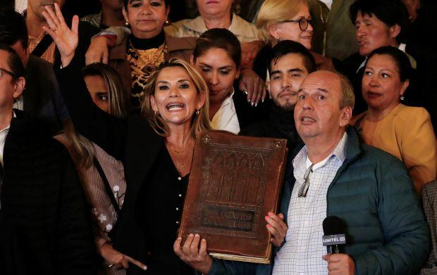 Bolivian Senator Jeanine Anez brandishes a massive bible outside Bolivia's presidential palace, having declared herself president.