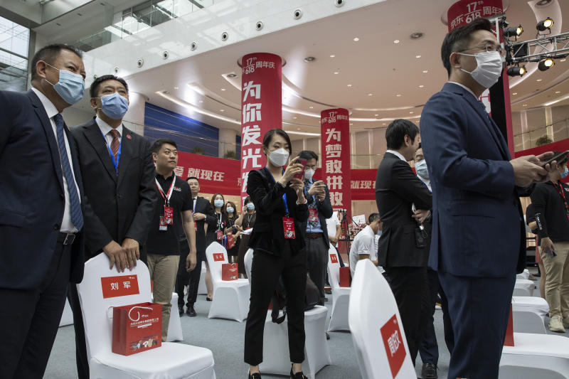 Attendees wear masks to curb the spread of the new coronavirus before the ceremony to mark the listing of JD.com on the Hong Kong Stock Exchange at the JD.com headquarters in Beijing on Thursday, June 18, 2020. Chinese e-commerce firm JD.com's stock jumped nearly 6% on its debut in Hong Kong on Thursday after the firm raised $3.9 billion in a share sale. (AP Photo/Ng Han Guan)