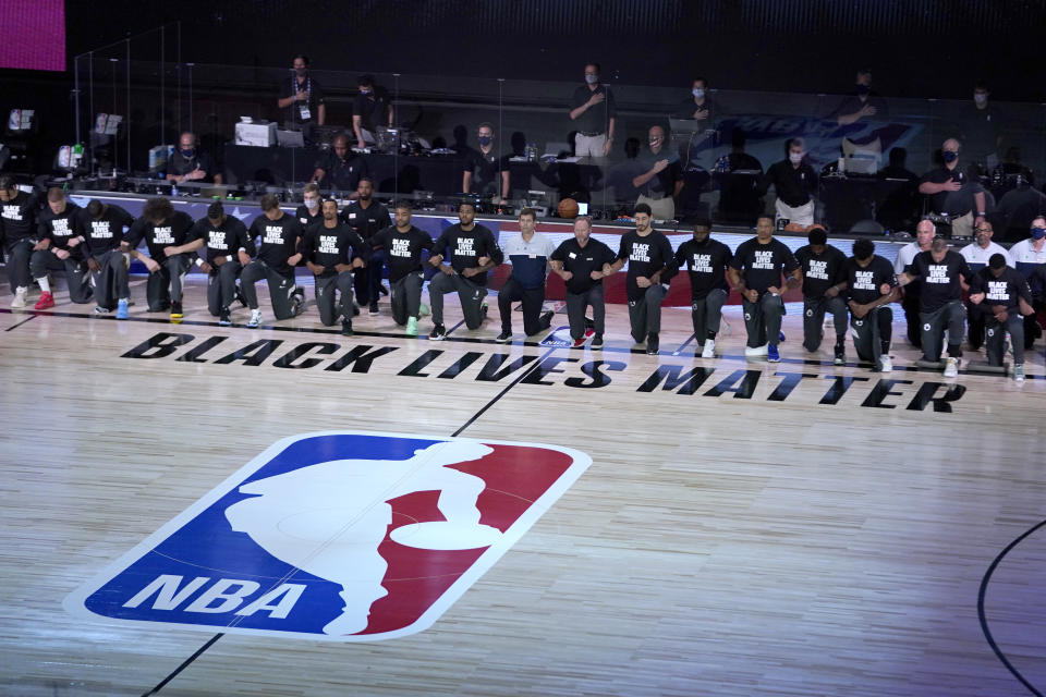 LAKE BUENA VISTA, FL - JULY 31: Members of the Milwaukee Bucks and the Boston Celtics kneel around a Black Lives Matter logo before the start of an NBA basketball game Friday, July 31, 2020, in Lake Buena Vista, Florida. NOTE TO USER: User expressly acknowledges and agrees that, by downloading and or using this photograph, User is consenting to the terms and conditions of the Getty Images License Agreement. (Photo by Ashley Landis-Pool/Getty Images)