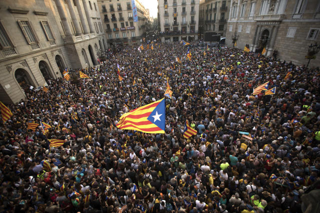 "<p>People wave ""estelada"" or pro independence flags outside the Palau Generalitat in Barcelona, Spain, after Catalonia's regional parliament passed a motion with which they say they are establishing an independent Catalan Republic, Friday, Oct. 27, 2017. (Photo: Emilio Morenatti/AP) </p>"