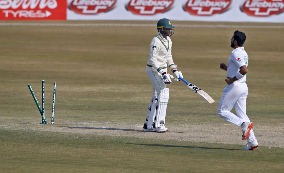 South Africa's Keshav Maharaj, center, reacts while he is bowled by Pakistan's Hasan Ali, right, during the third day of the second cricket test match between Pakistan and South Africa at the Pindi Stadium in Rawalpindi, Pakistan, Saturday, Feb. 6, 2021. (AP Photo/Anjum Naveed)