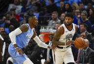 Los Angeles Clippers forward Paul George, right, tries to drive past Minnesota Timberwolves forward Robert Covingtonduring the first half of an NBA basketball game Friday, Dec. 13, 2019, in Minneapolis. (AP Photo/Craig Lassig)