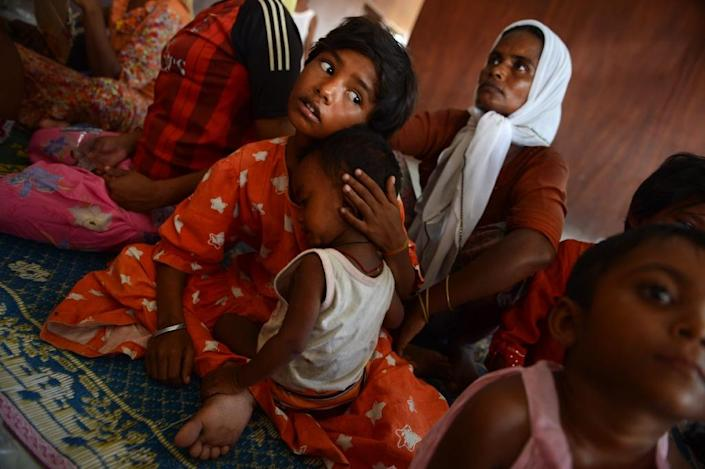 A Rohingya girl from Myanmar holds her younger sibling at a new confinement area at Bayeun, Aceh province on May 21, 2015 after more than 400 Rohingya migrants from Myanmar and Bangladesh were rescued by Indonesian fishermen (AFP Photo/Romeo Gacad)