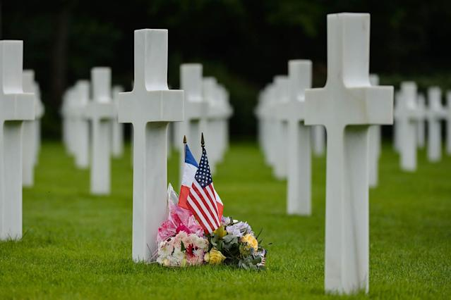 <p>French and U.S. flags near the graves of fallen soldiers at the Normandy American Cemetery, which contains the remains of 9,387 American military dead, most killed during the invasion of Normandy and ensuing military operations in World War II. (Photo: Artur Widak/NurPhoto via Getty Images) </p>