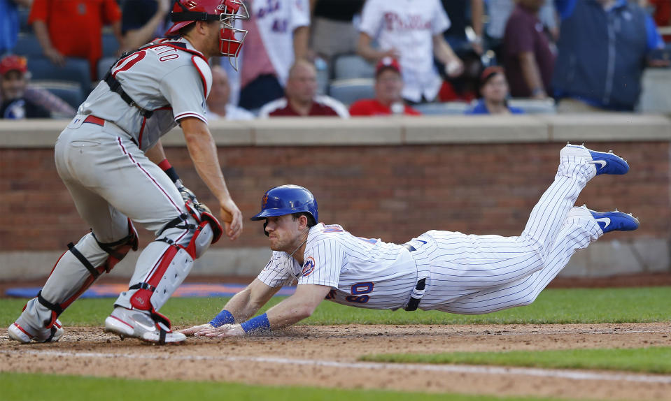 New York Mets right fielder Billy McKinney (60) scores the game winning run against the Philadelphia Phillies, on a sacrifice fly by Mets fielder Michael Conforto during the ninth inning of a baseball game Saturday, June 26, 2021, in New York. (AP Photo/Noah K. Murray)