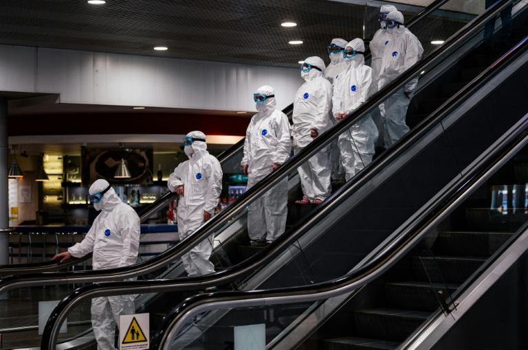 Medical staff wearing protective suits ride down an escalator at Moscow's Sheremetyevo airport (AFP Photo/Dimitar DILKOFF)