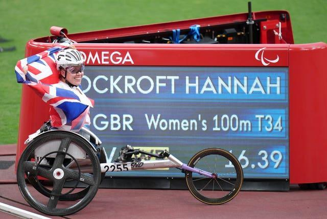 Hannah Cockroft poses with the scoreboard showing her new world record