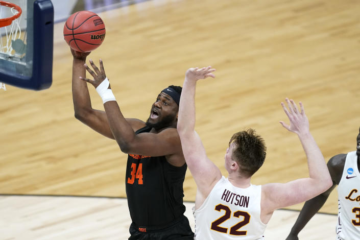 Oregon State forward Rodrigue Andela (34) drives to the basket past Loyola Chicago center Jacob Hutson (22) during the first half of a Sweet 16 game in the NCAA men's college basketball tournament at Bankers Life Fieldhouse, Saturday, March 27, 2021, in Indianapolis. (AP Photo/Darron Cummings)