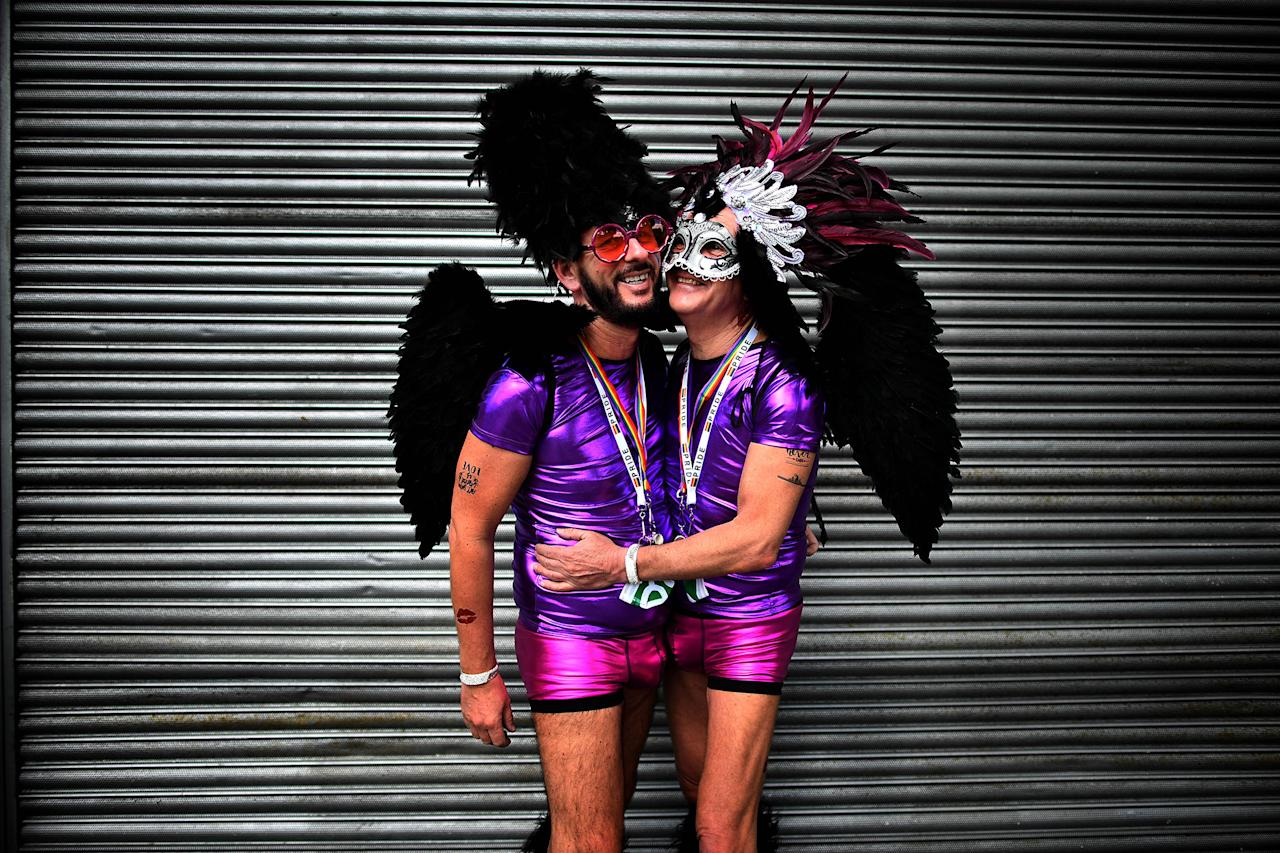 <p>A gay couple embrace as they watch the Belfast Gay Pride march taking place on August 5, 2017 in Belfast, Northern Ireland. (Photo: Charles McQuillan/Getty Images) </p>