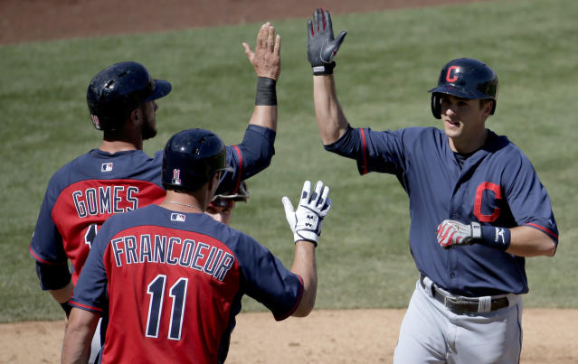 Cleveland Indians's Lonnie Chisenhall, right, celebrates his two-run home run with Yan Gomes, left, and Jeff Francoeur during the fourth inning of a spring exhibition baseball game against the Arizona Diamondbacks in Scottsdale, Ariz., Tuesday, March 11, 2014. (AP Photo/Chris Carlson)