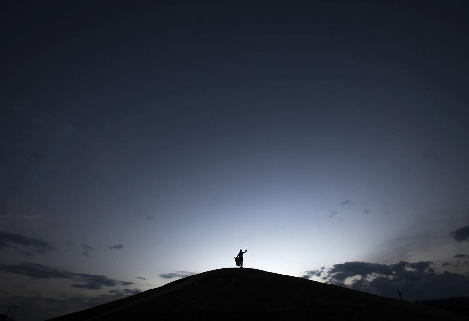 A child stands at the top of Cardboard Hill to get one last ride before dark at Renaissance park on Tuesday, March 30, 2021, in Chattanooga, Tenn. (Troy Stolt/Chattanooga Times Free Press via AP)