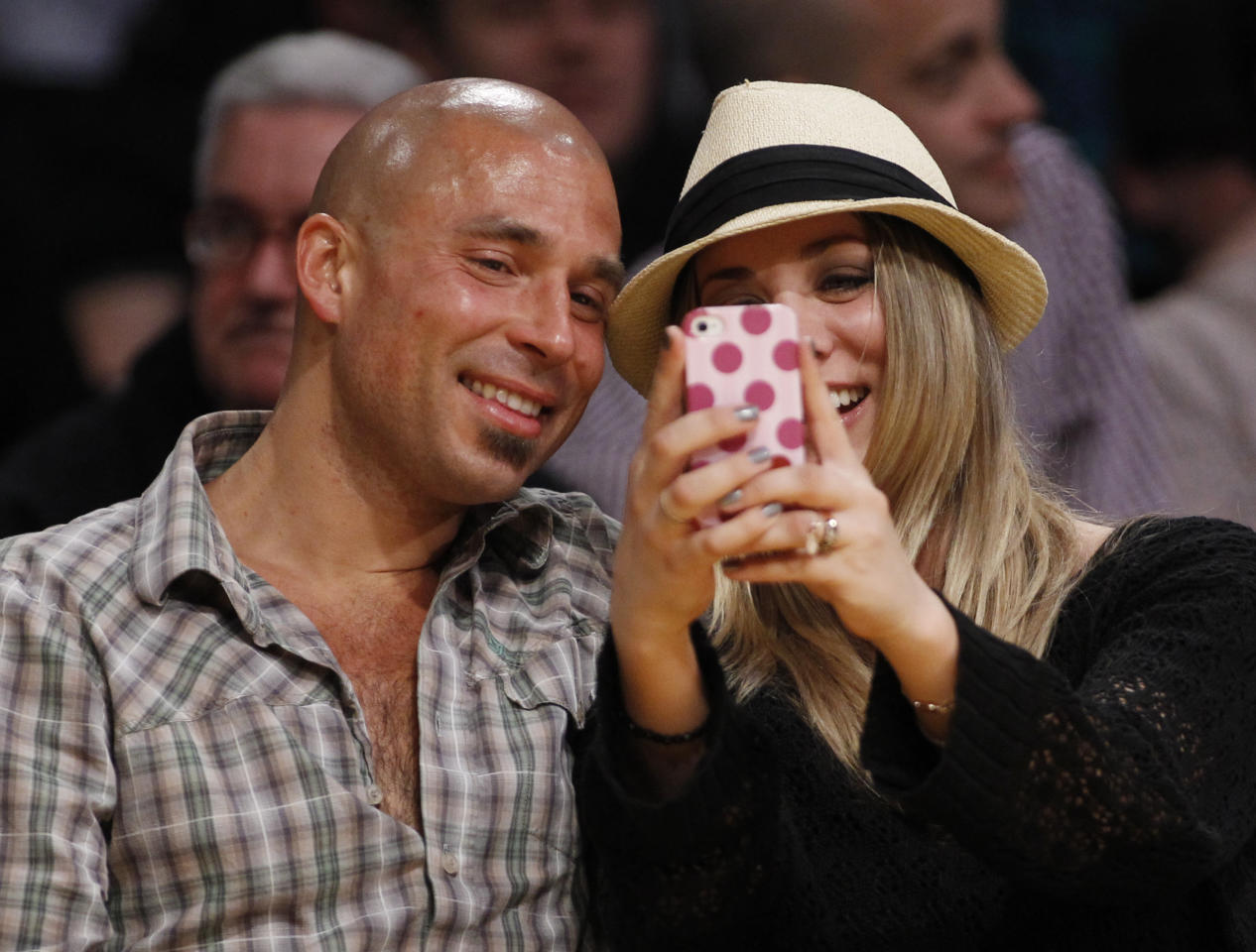 In this March 23, 2012, file photo, Actress Kaley Cuoco uses a mobile phone as she sits with an unidentified man courtside at the NBA basketball game between the Portland Trail Blazers and Los Angeles Lakers in Los Angeles. The Electronic Entertainment Expo conference, which officially starts Tuesday, June 5, 2012, in Los Angeles, is still the place to showcase all the big blockbusters and flashy console games, but games for smartphones and tablets are increasingly in the minds of game developers. (AP Photo/Danny Moloshok, File)
