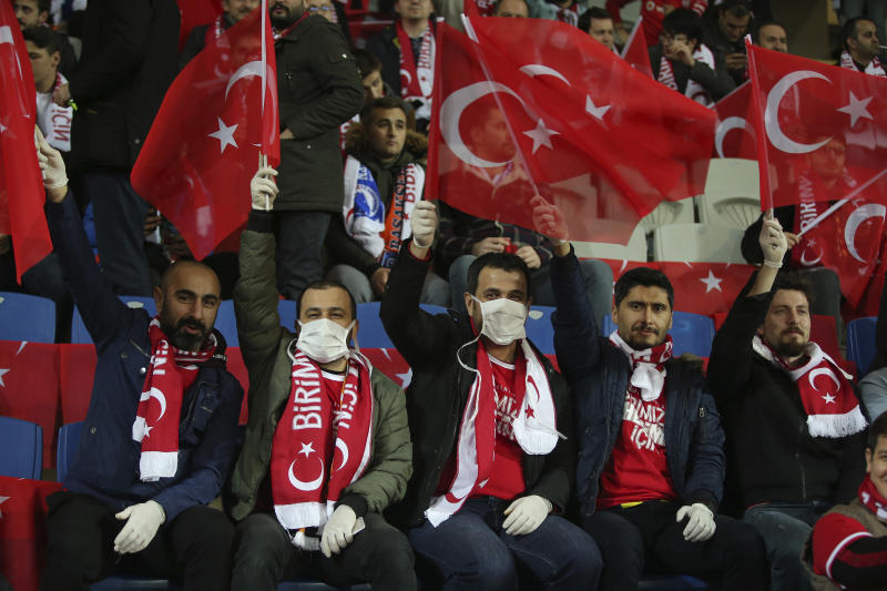 FILE - In this Thursday, March 12, 2020 file photo spectators, some wearing masks because of the coronavirus outbreak, wave Turkish flags prior to a Europa League top 16 first leg soccer match between Basaksehir and Copenhagen, in Istanbul. (AP Photo, File)