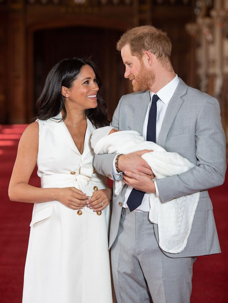 Meghan Markle and husband, Prince Harry share a beautiful smile while he is holding on to their new born baby.