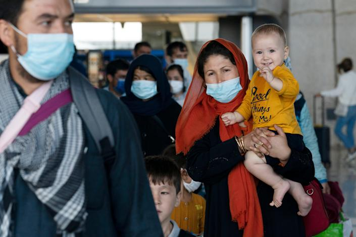 Families evacuated from Kabul, Afghanistan, walk through the terminal before boarding a bus after they arrived at Washington Dulles International Airport, in Chantilly, Virginia, on Aug. 24, 2021.