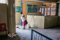 A worker at the Lycee Petion-Ville in Port-au-Prince cleans an office as schools across Haiti prepare to reopen