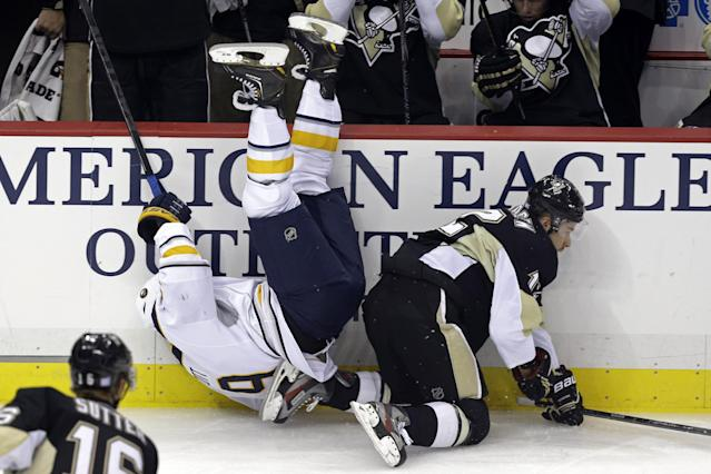 Buffalo Sabres' Steve Ott (9) tumbles to the ice after a collision with Pittsburgh Penguins' Chuck Kobasew (12) in the first period of an NHL hockey game in Pittsburgh on Saturday, Oct. 5, 2013. (AP Photo/Gene J. Puskar)