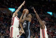 Golden State Warriors guard Jacob Evans, center, shoots between Portland Trail Blazers guard Anfernee Simons, left, and forward Anthony Tolliver during the second half of an NBA basketball game in Portland, Ore., Wednesday, Dec. 18, 2019. The Trail Blazers won 122-112. (AP Photo/Craig Mitchelldyer)