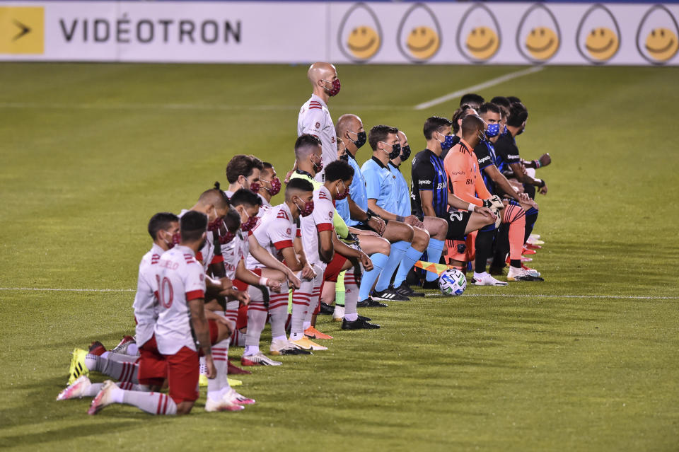MONTREAL, QC - AUGUST 28:  Michael Bradley #4 of Toronto FC stands while his teammates and members of the Montreal Impact kneel during the pre-game ceremony of the MLS game at Saputo Stadium on August 28, 2020 in Montreal, Canada. (Photo by Minas Panagiotakis/Getty Images)