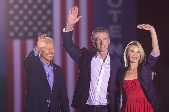 Joe Biden stands with Gavin Newsom and Jennifer Siebel Newsom during a campaign event to keep the California governor in office on 13 September.