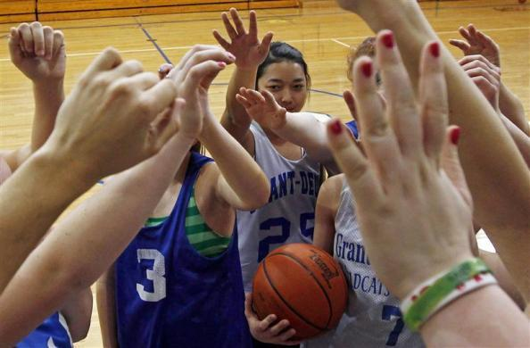 Jutarat Sawatpoon (C), a foreign exchange student from Thailand, joins teammates on the Grant-Deuel School girls' junior varsity basketball team for a cheer after a practice in Revillo, South Dakota February 13, 2012.