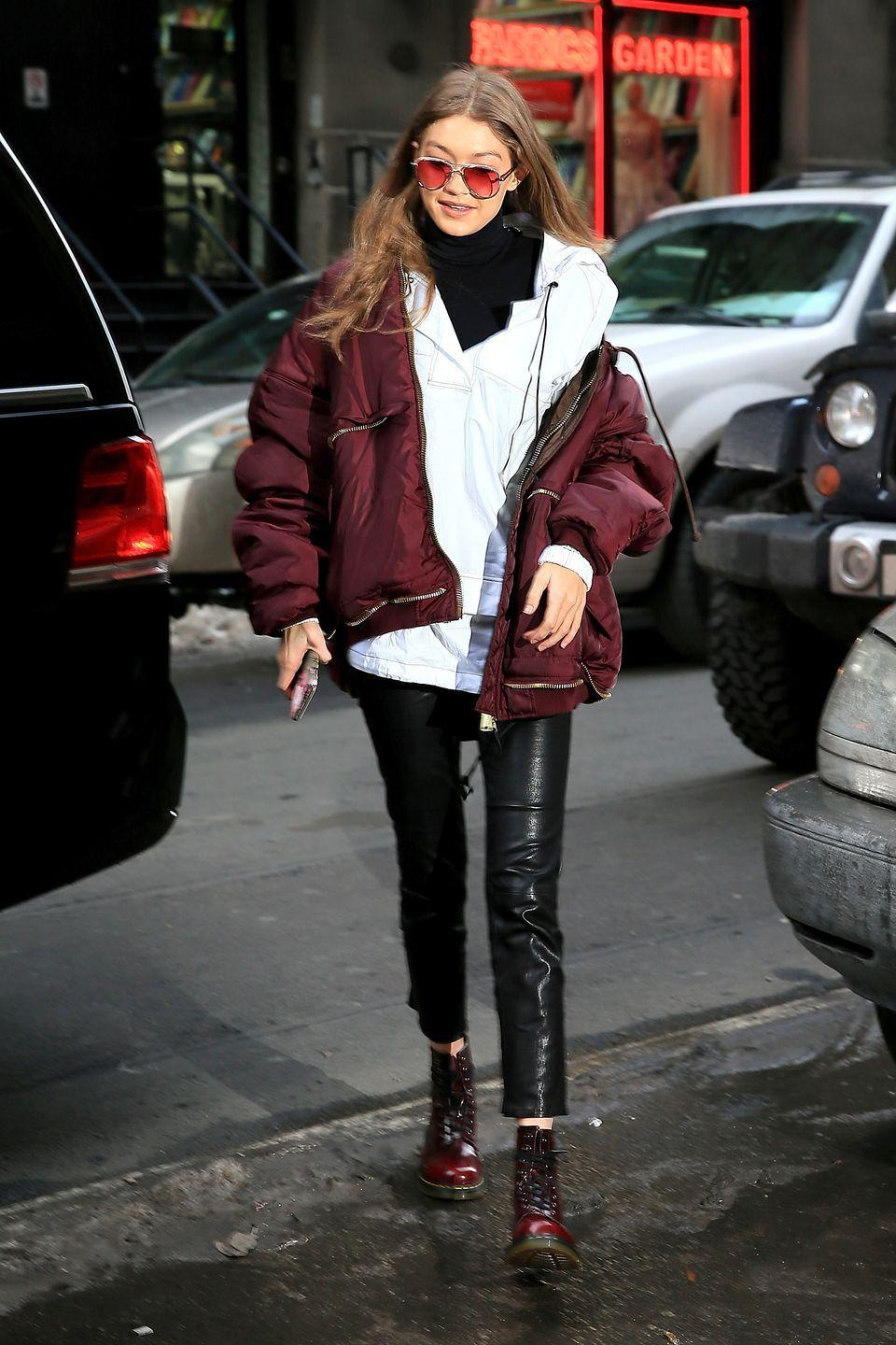 <p>In a maroon parka, Bassike white hoodie, black turtleneck, leather pants, red Doc Martens and red tinted sunglasses while out in New York. </p>