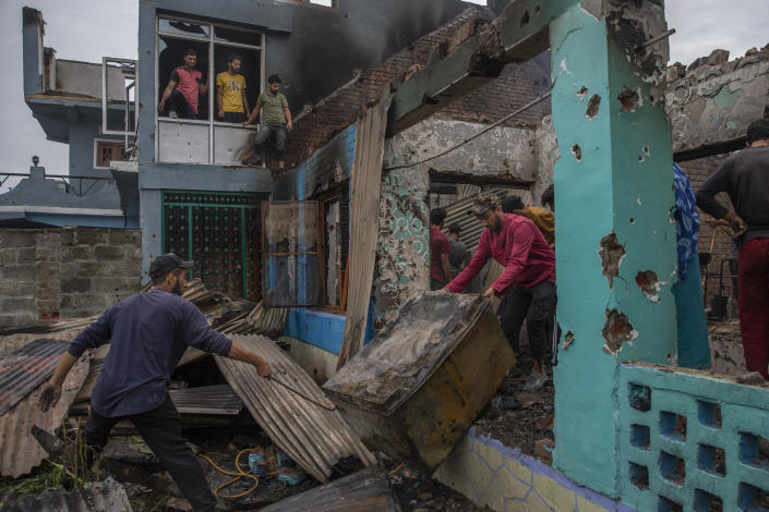 Kashmiri villagers salvage a metal box as they clear a house destroyed in a gunfight in Pulwama, south of Srinagar, Indian controlled Kashmir, Wednesday, July 14, 2021. Three suspected rebels were killed in a gunfight in Indian-controlled Kashmir on Wednesday, officials said, as violence in the disputed region increased in recent weeks. Two residential houses were also destroyed. (AP Photo/ Dar Yasin)