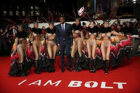 "Athlete Usain Bolt (C) poses for photographers with dancers at the world premiere of the film ""I am Bolt"" in London"