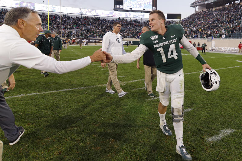 Michigan State quarterback Brian Lewerke (14) is congratulated by coach Mark Dantonio, left, an NCAA college football game against Indiana, Saturday, Sept. 28, 2019, in East Lansing, Mich. (AP Photo/Al Goldis)