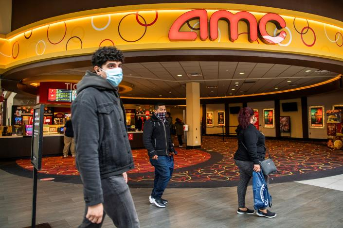 People wear face masks as they walk by a movie theater during the coronavirus disease (COVID-19) pandemic in Newport, New Jersey, U.S., April 2, 2021. REUTERS/Eduardo Munoz