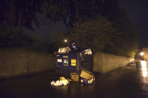 Robin Pickell, 23, a practicing 'freegan,' sorts through a dumpster for edible food in an alley behind in Vancouver, British Columbia April 26, 2012.