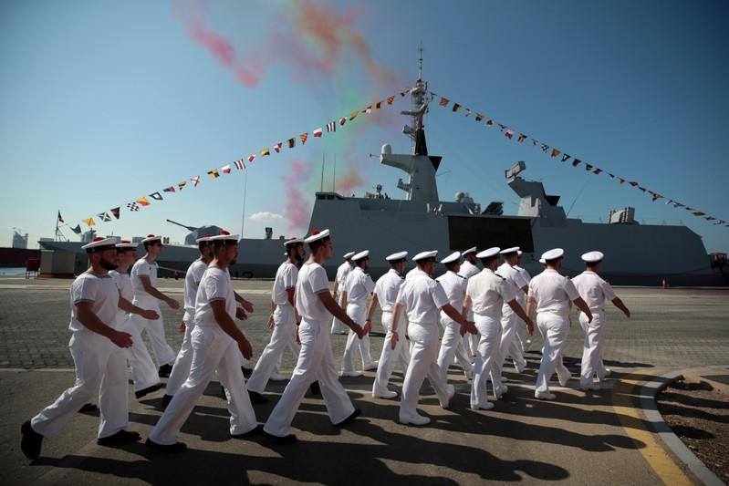 Members of the French Navy march past the French frigate Courbet while taking part in a military cermony at the French Naval Base in Abu Dhabi