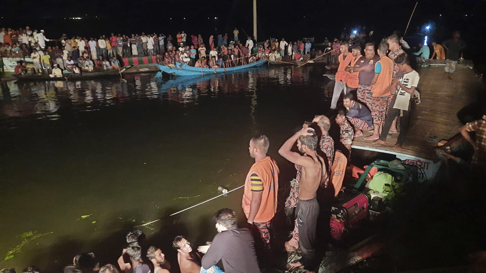 People watch rescue work after a passenger boat carrying more than 100 people sank after a collision in a large pond in Brahmanbaria district, Bangladesh, Friday, Aug. 27, 2021. The sinking occurred in the Bijoynagar area in Brahmanbaria district in the evening, local police official Imranul Islam said by phone. Rescuers recovered at least 21 bodies by late Friday. (AP Photo)