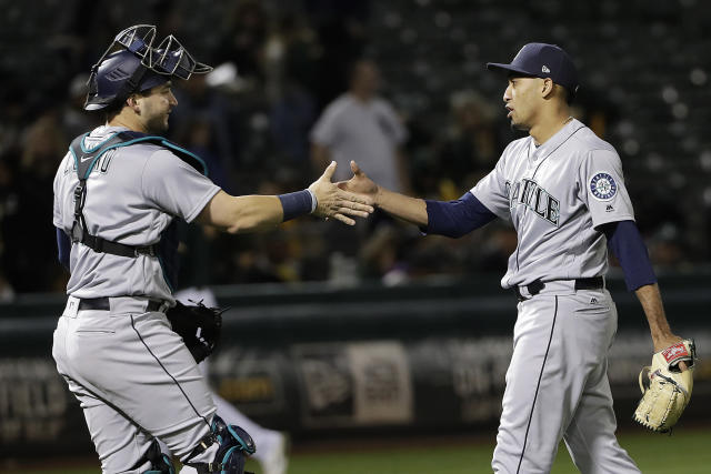 Seattle Mariners catcher Mike Zunino, left, celebrates with pitcher Edwin Diaz after the Mariners beat the Oakland Athletics 1-0 in a baseball game in Oakland, Calif., Wednesday, May 23, 2018. (AP Photo/Jeff Chiu)