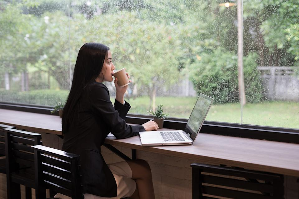 Businesswoman Drinking Coffee While Sitting At Desk In Office