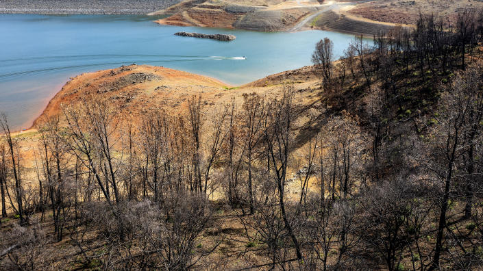 Below a hillside scorched in the 2020 North Complex Fire, a boat crosses Lake Oroville on Saturday, May 22, 2021, in Oroville, Calif. At the time of this photo, the reservoir was at 39 percent of capacity and 46 percent of its historical average. California officials say the drought gripping the U.S. West is so severe it could cause one of the state's most important reservoirs to reach historic lows by late August, closing most boat ramps and shutting down a hydroelectric power plant during the peak demand of the hottest part of the summer. (AP Photo/Noah Berger)