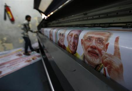 A worker operates a machine to print banners of Hindu nationalist Modi, prime ministerial candidate for India's main opposition BJP ahead of the general elections in Ghaziabad
