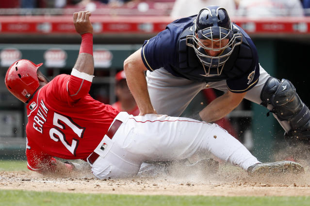 Cincinnati Reds' Phillip Ervin (27) scores against Milwaukee Brewers catcher Erik Kratz, right, on an RBI double by Dilson Herrera off starting pitcher Wade Miley in the seventh inning of a baseball game, Thursday, Aug. 30, 2018, in Cincinnati. (AP Photo/John Minchillo)