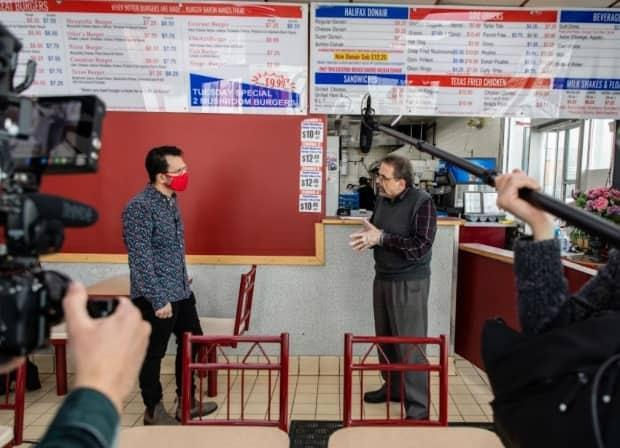 Omar Mouallem interviews Khaled Kamaleddine, one of the owners of a Burger Baron restaurant in Edmonton, for his forthcoming documentary, The Last Baron.  (Amber Bracken - image credit)
