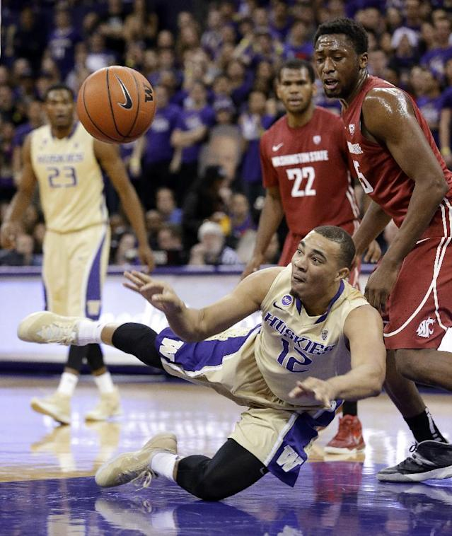 Washington's Andrew Andrews (12) gets off a pass as he tumbles to the floor in front of Washington State's Royce Woolridge (22) and Junior Longrus during the first half of an NCAA men's college basketball game Friday, Feb. 28, 2014, in Seattle. (AP Photo/Elaine Thompson)