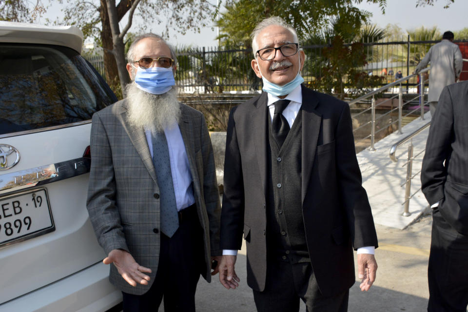 Mehmood A. Sheikh, right, defense lawyer, and Ahmed Saeed Sheikh, father of British-born Pakistani Ahmed Omar Saeed Sheikh, leave the Supreme Court after an appeal hearing in the Daniel Pearl case in Islamabad, Pakistan, Thursday, Jan. 28, 2021. The court on Thursday has ordered the release of Sheikh convicted and later acquitted in the gruesome beheading of American journalist Daniel Pearl in 2002. The court also dismissed an appeal of Sheikh's acquittal by Pearl's family. (AP Photo/Waseem Khan)