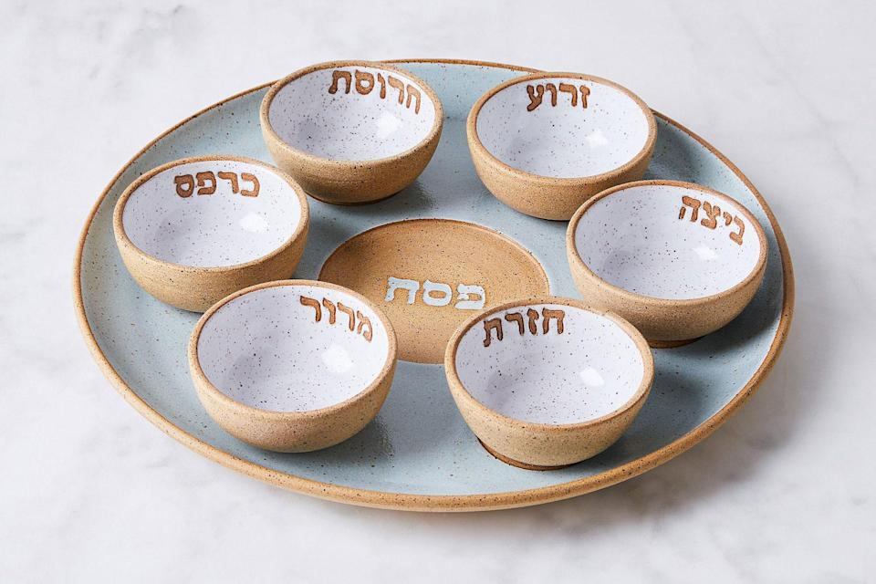 """<p>Designed and created in her small studio in Brooklyn, New York, Rachael Scharf's handmade Seder plate is made from speckled stoneware clay, glazed to perfection, and features hand-carved Hebrew lettering of the traditional foods for each bowl.</p> <p><em><strong>Shop Now:</strong> RachaelPots Handmade Seder Plate, $250, <a href=""""http://prf.hn/click/camref:1100liuTL/pubref:MSL10PassoverSederPlatesGuaranteedtoBecomeYourNextFamilyHeirloomachurchiPasGal8067612202103I/destination:https%3A%2F%2Ffood52.com%2Fshop%2Fproducts%2F7238-handmade-seder-plate%3Fsku%3D22557"""" rel=""""sponsored noopener"""" target=""""_blank"""" data-ylk=""""slk:food52.com"""" class=""""link rapid-noclick-resp"""">food52.com</a>.</em></p>"""