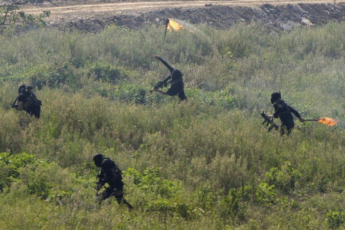 Participants playing the role of terrorists attack a United Nations base during the Shared Destiny 2021 drill at the Queshan Peacekeeping Operation training base in Queshan County in central China's Henan province Wednesday, Sept. 15, 2021. Peacekeeping troops from China, Thailand, Mongolia and Pakistan took part in the 10 days long exercise that field reconnaissance, armed escort, response to terrorist attacks, medical evacuation and epidemic control. (AP Photo/Ng Han Guan)