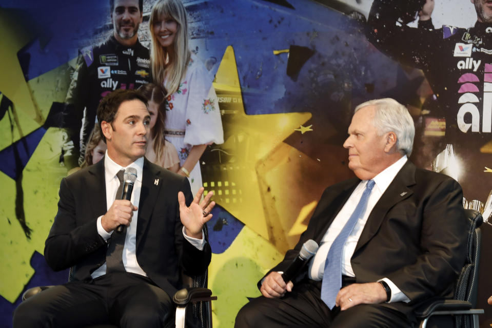 Jimmie Johnson, left, looks to team owner Rick Hendrick as he answers a reporter's question during his NASCAR retirement announcement at Hendrick Motorsports near Charlotte, N.C., Thursday, Nov. 21, 2019. (AP Photo/Bob Leverone)