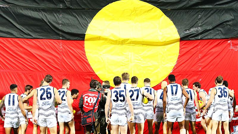 Pictured here, players walk out for a match during the AFL's Indigenous Round.