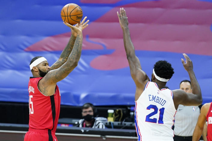 Houston Rockets' DeMarcus Cousins, left, goes up for a shot against Philadelphia 76ers' Joel Embiid during the first half of an NBA basketball game, Wednesday, Feb. 17, 2021, in Philadelphia. (AP Photo/Matt Slocum)